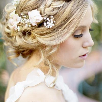 Braided crown hairstyle for wedding day with flowers and low bun 1